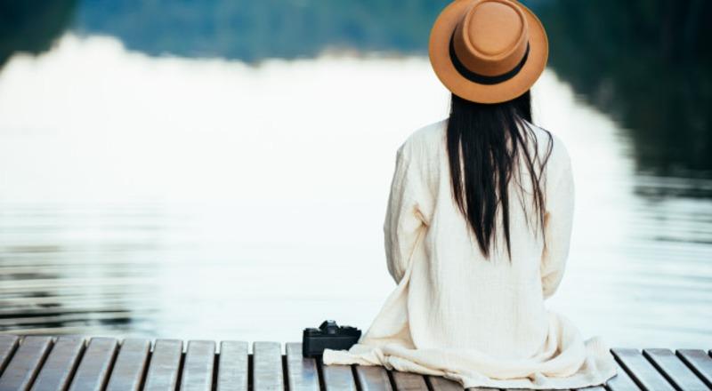 Mujer sentada en la orilla de un río