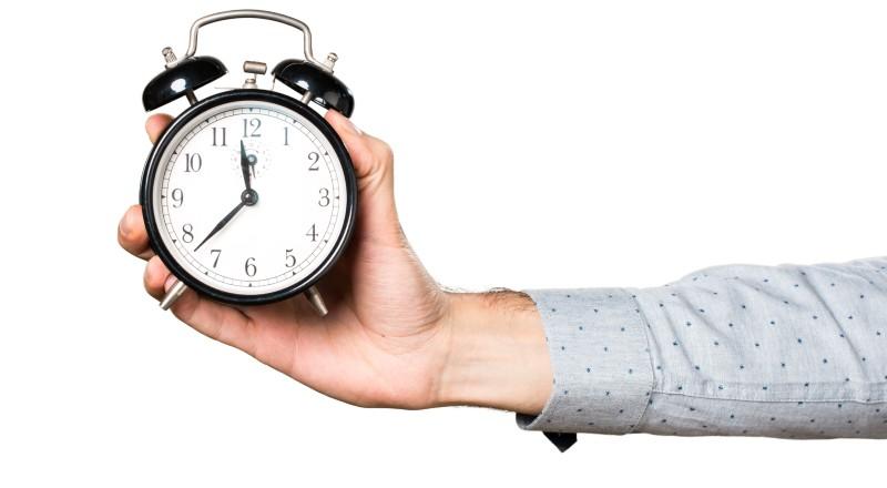 Una persona tomando un reloj en su mano
